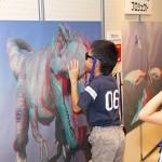 飛び出す3D恐竜展ポスターに夢中の子どもたち